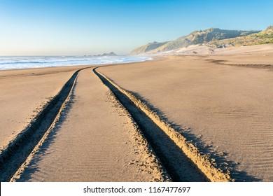 A 4WD car track in a wild beach sand going towards an endless infinite horizon at the Chilean coastline in Topocalma beach, Puertecillo, Chile