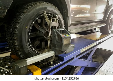 4WD car undergo wheel align in garage with precision alignment equipment