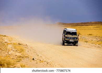 4x4 jeep driving high speed at a dirt road in the african savannah with dust in the background, yellow grassland on the side and blue sky in the background