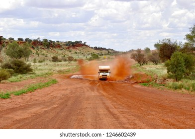 4x4 offroad camper van driving through floodway in the australian outback on mereenie loop road with red sand gravel road