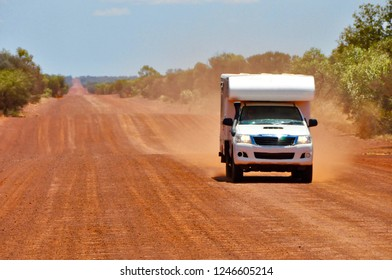 4x4 offroad camper van driving on red sand gravel road highway creating dust in australia outback on a sunny day with blue sky and no clouds