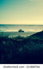 4x4 RV van on deserted beach. Driving towards the sun, leaving a nice shadow. Freedom feeling, cruising the beach with a packed car.