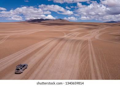 4x4 SUV in All Terrain Vehicle Tracks in Altiplano Desert near Uyuni, Bolivia. Aerial Drone Scene