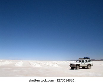 A 4x4  tour vehicle parked next to the salt hills in a salt mine near Uyuni town in Salar de Uyuni, Bolivia. Salar de Uyuni is the world's largest salt flat.