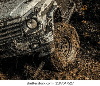 4x4 travel trekking. Bottom view to big offroad car wheel on country road and mountains backdrop. Safari suv. Offroad vehicle coming out of a mud hole hazard. Off-road vehicle goes on mountain way