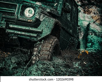 4x4 travel trekking. Offroad vehicle coming out of a mud hole hazard. Bottom view to big offroad car wheel on country road and mountains backdrop
