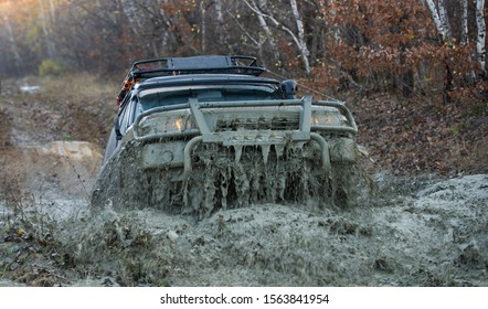 4x4 travel trekking. Track on mud. Off-road vehicle goes on the mountain. Mud and water splash in off road racing. Safari. Offroad. Adventure travel. Off-road travel on mountain road. Offroad vehicle