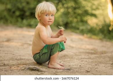 Un garçon de 4 ans pieds nus en short court le long d'un chemin forestier près de la rivière.