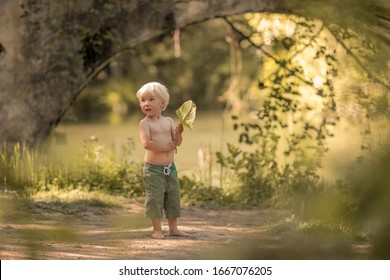 A 4-year-old boy barefoot in shorts runs along a forest path near the river.
