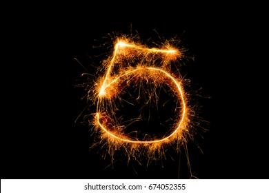 5 5th  five number from sparkler on black background.
