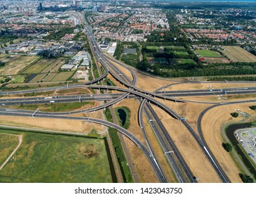 5 August 2018, Den Haag, Holland. Aerial view of a multilevel cloverleaf with underpass, overpass and railway. It is the intersection were highway A4 and motorway A12 connect with skyline The Hague.