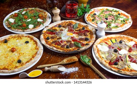 5 bio pizza: cheese, tomato, eastern, salad, vegetarian, mozzarella, romana. Presented with spicy oil and several decorative elements. Served on a round wooden table.