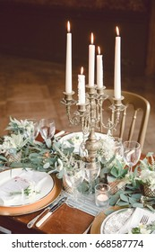 5 candelabra on a table with green garland and gold chairs.