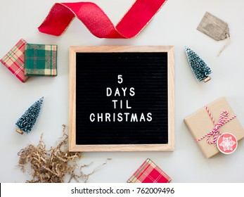 5 Days Til Christmas. Christmas countdown on a black letter board with wooden frame surrounded by holiday objects.