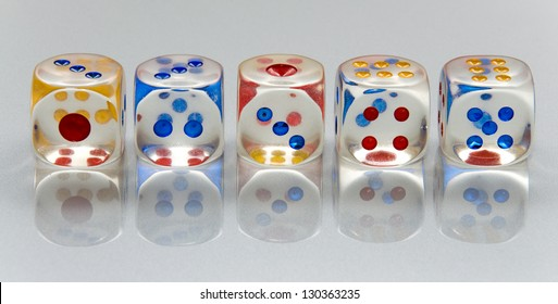 5 dices on the gray and reflexive table.
