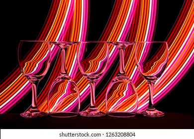 5 empty wine glasses isolated on a black background with colorful orange red and pink neon light streaks behind them