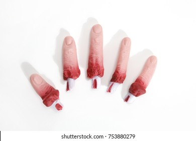 5 fake bloodied plastic fingers as if they had been torn off on a white background. reconstituted hand. Minimal still life photography