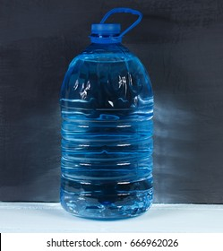 5 liters. Big plastic bottle of potable water, barrel with handle on a dark background