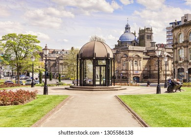 5 May 2016: Harrogate, North Yorkshire, England, UK - The Festival Pavilion in Crescent Gardens, with its statues of Cupid and Psyche, sculpted in 1861 by Italian artist Benzonni, and the Royal Baths.