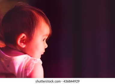 A 5 month old baby watching a dance show from back stage.