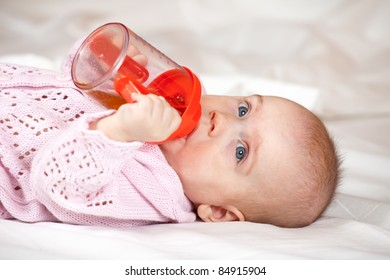 5 months baby girl laying witn baby bottle on white sheet
