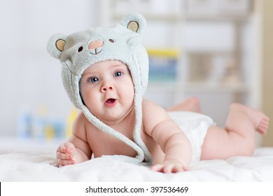 5 months baby girl weared in funny hat lying down on a blanket.