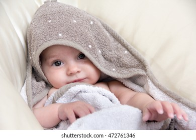 5 months old baby girl from Slovenia covered with towel after bathing