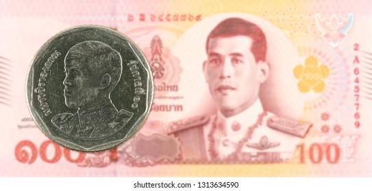 5 new thai baht coin against 100 new thai baht banknote