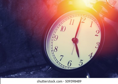 5 o'clock vintage clock at dark color tone with sun light memory time concept.
