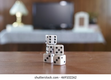5 pieces of game dice stacked together on a table with a TV and other living room things blurred in the background.