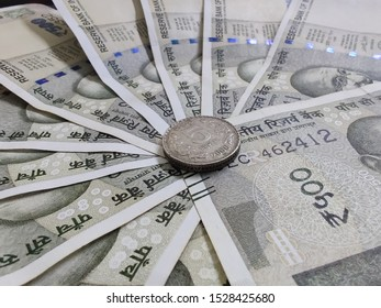 5 rupee coin placed at center of circular distributed 500 Indian rupees bank notes