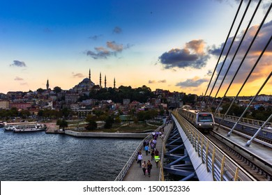 5 September 2019; Istanbul, Turkey, People crossing the Golden Horn (Halic) Metro Bridge in a cloudy day during sunset. Bridge connects the Beyoğlu and Fatih districts on the European side of Istanbul