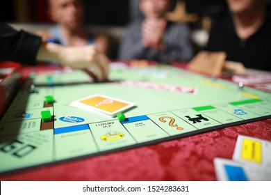 5 September 2019:Group of people playing Monopoly board game together at night.Friends with funny emotions enjoying the game in evening.At home game.