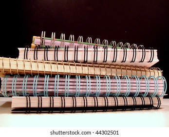 5 spiral-bound notebooks stacked on black and white background.