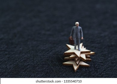 5 stars business, success winning or excellence satisfaction concept, miniature figure confidence businessman holding briefcase standing on stack of stars on dark black background with copy space.