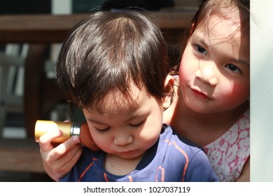 5 year old Asian girl Wearing Makeup and try to put the brush on her sibling,younger brother.Respect kids for the way they express themselves.Let her be natural. Girl always passion in cosmetic.