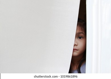 5 year old Asian little girl sneak peek or looking through the cap of window blind or curtain. Curiously girl look sad,bored but interesting outside things.She may sick or imprison.