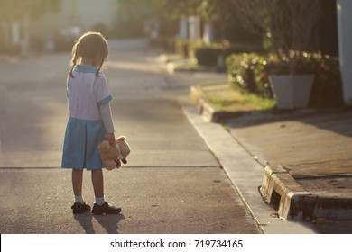 5 year old Asian little girl stand alone at the street,lonely with her doll.Loneliness is common when kid start pre-school or big life changes.Kid have no friends ,they say that nobody likes them.