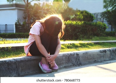 5 year old Asian little girl sit alone at the street in the evening.Girl hide her face on her knees,she may crying or ignoring.Concept of lonely child or kid in trouble or kid violence.