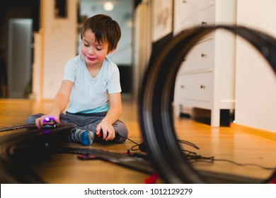 5 year old blond boy is playing with slot car model racing track indoor