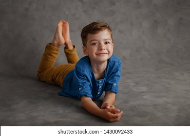 5 year old boy blue shirt and yellow pants studio portrait on gray background.