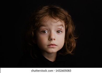 5 year old boy with long hair studio portrait on black background