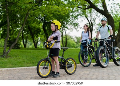 5 year old boy sitting on his bike in front of his family