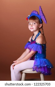 5 Year old girl with dancing costume on a brown background