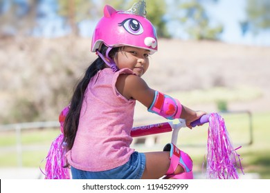 5 year old girl getting ready to ride away in her pink bike, wearing protective helmet and knee pads at a park with hills