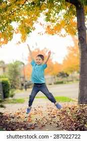 5 year old mixed race Asian Caucasian boy does a star jump (jumping jack) on the footpath (sidewalk) of his suburban neighborhood in Autumn (Fall)