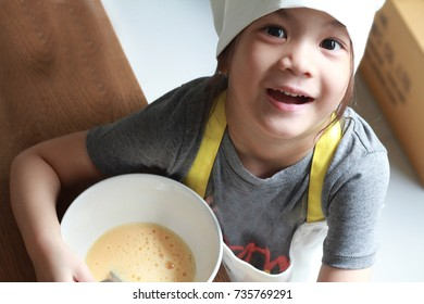 5 years old Asian little girl preparing by beating eggs for her omelet.Get your kids involved in the cooking with simple before moving on master skills.Fun,created and challenge.