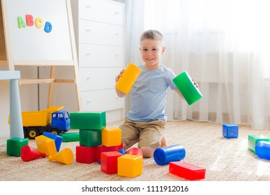 5 years old boy sitting on the floor playing with colorful plastic blocks. Creativity educational toys for preschoolers