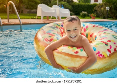5 years old Boy in swimming pool smiling and enjoying on inflatable colorful ring looks like donut during nice summer day at his home garden