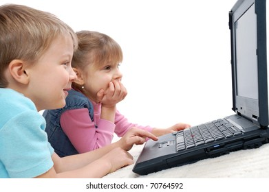 5 years old girl and boy playing computer games lying on a floor